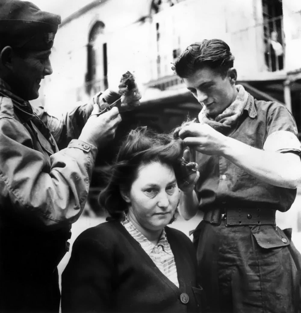 Soldiers cutting the hair of a collaborator on Bastille Day. August 12, 1944.