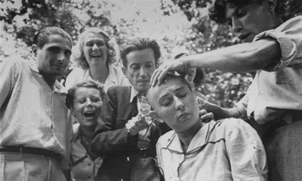 A crowd jeers as a woman's head is shaved during the liberation of Marseilles.