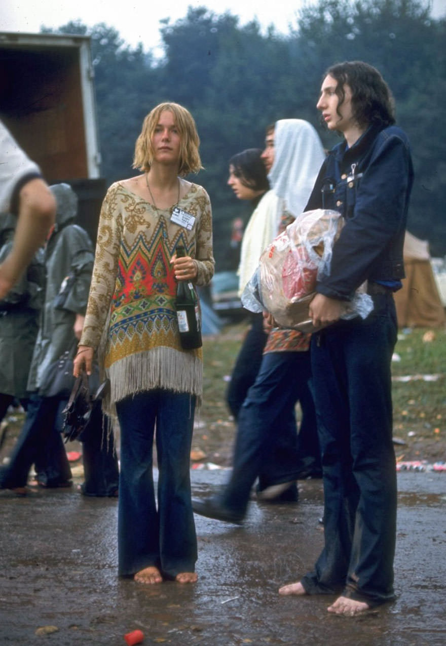 Hippie Couple Standing Barefoot On A Road Holding A Bundle & Wine Bottle At Woodstock
