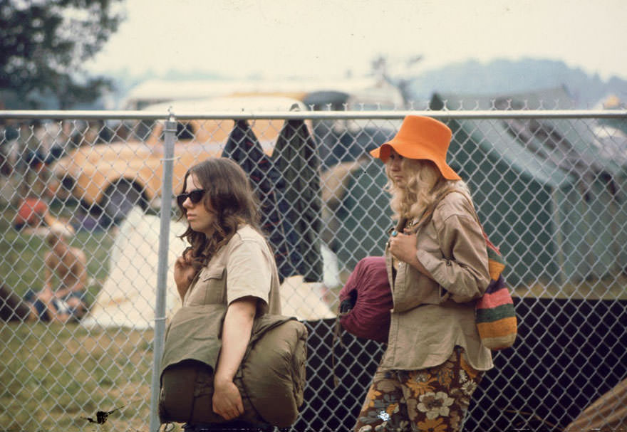 Two Young Women Walking Along The Fence With Sleeping Bags At The Woodstock Music Festival