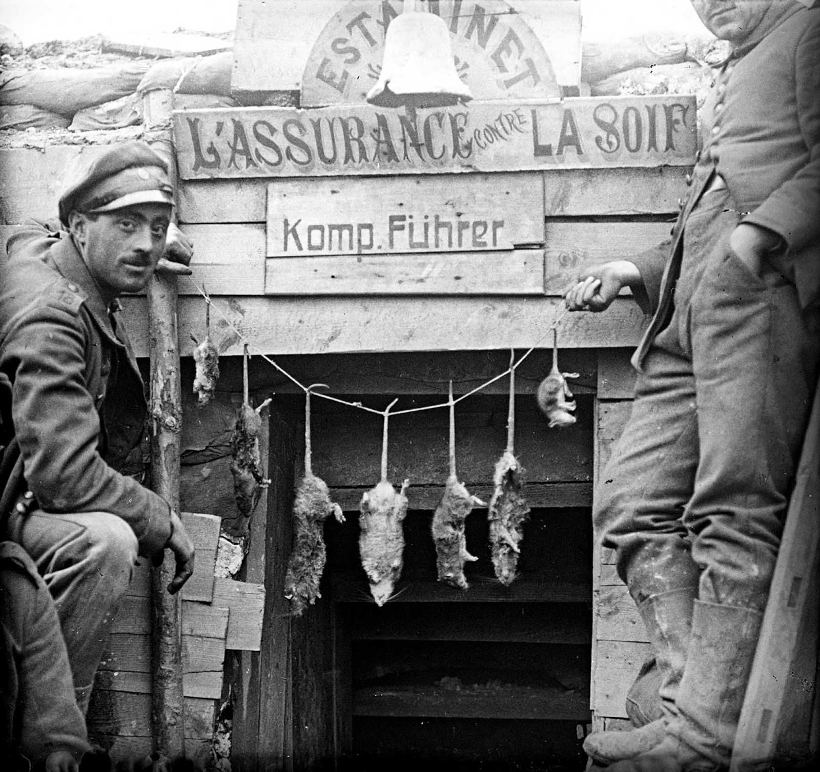 Two German soldiers posing with rats caught in their trench.