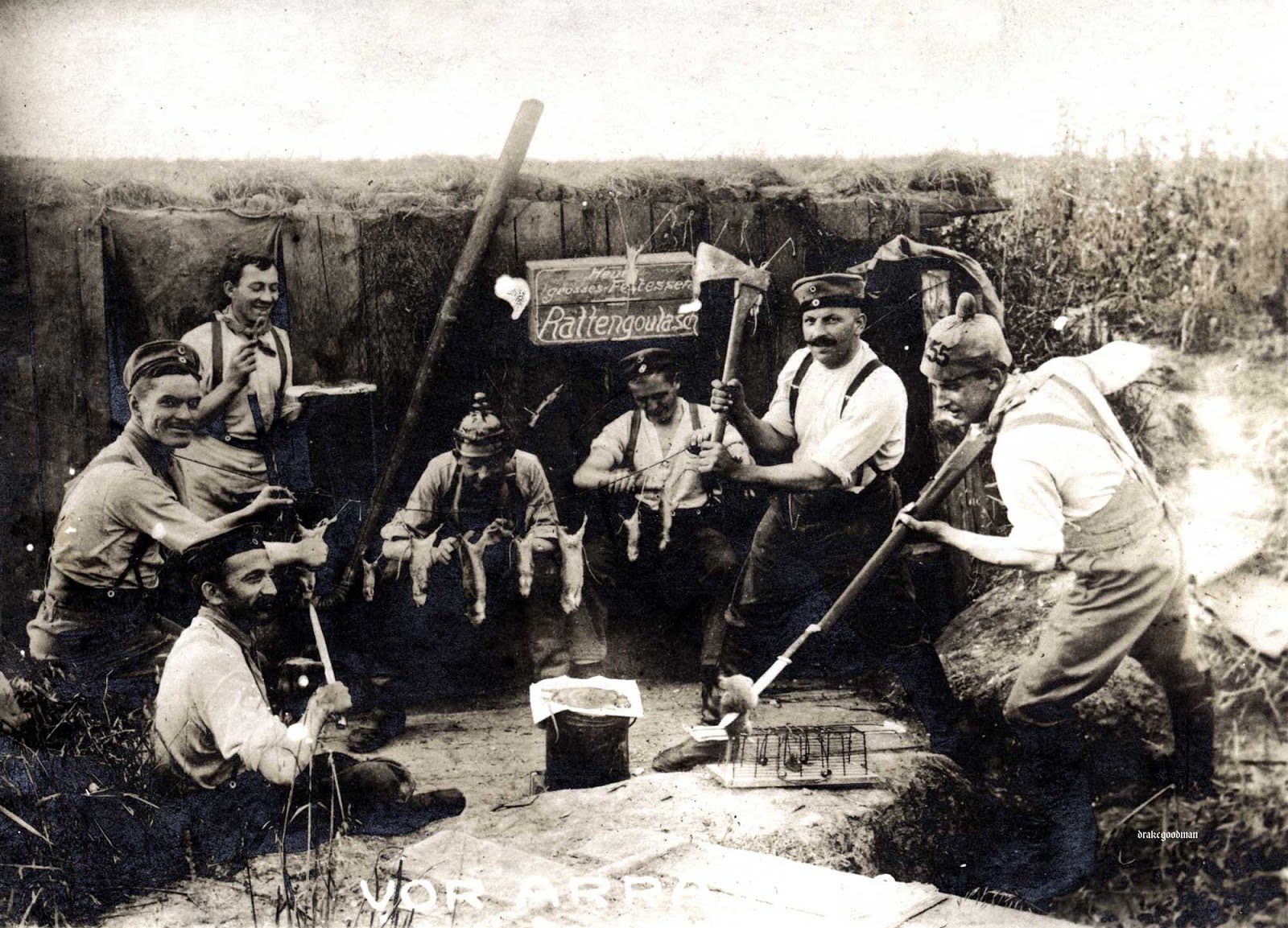 German artillerymen preparing several dead rats and one hapless mouse (or a skittish rat) for their evening repast.