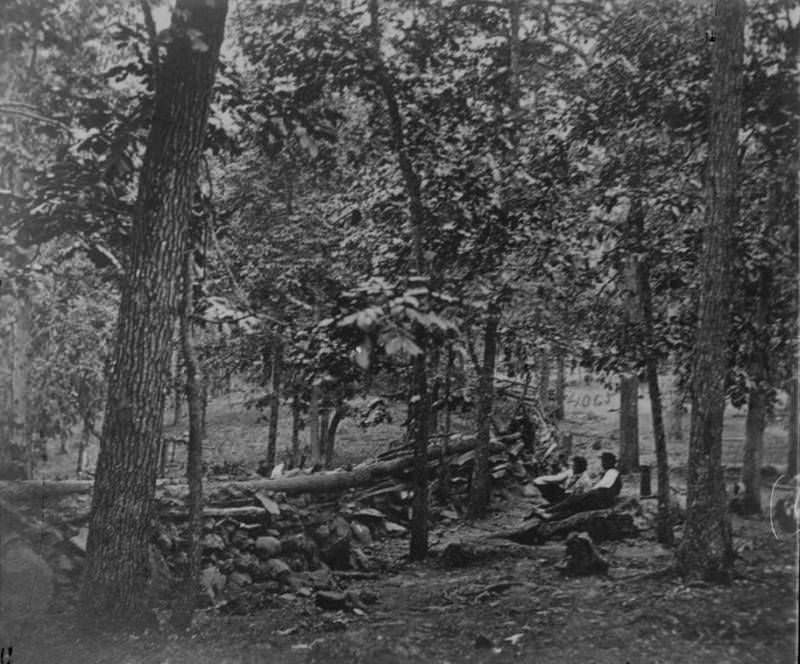 Two Union soldiers rest behind defensive fortifications during the Battle of Gettysburg.