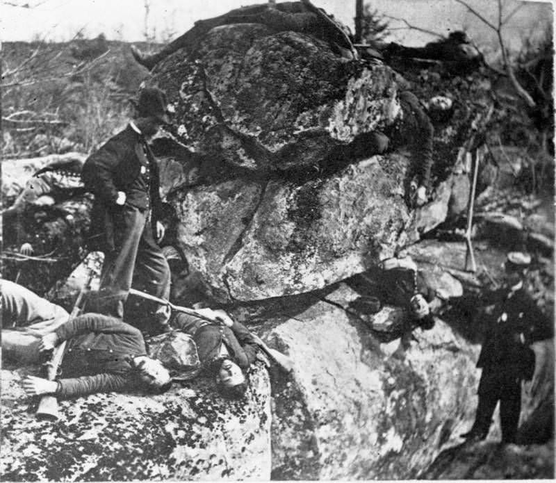 Men examine the bodies of two dead sharpshooters.