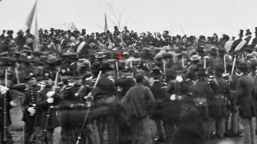 Abraham Lincoln (identified by red arrow) stands among the crowd before delivering the Gettysburg Address.