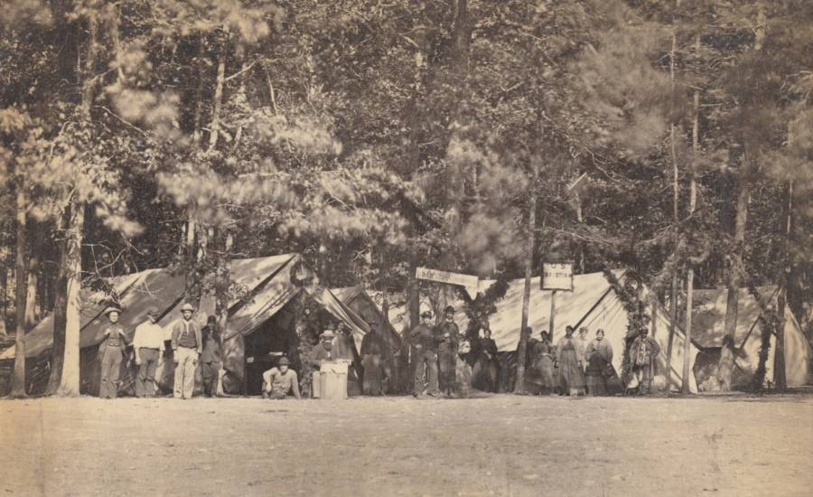 People stand in front of the Battle of Gettysburg tents belonging to the U.S. Christian Commission, a group that provided supplies and services to Union troops.