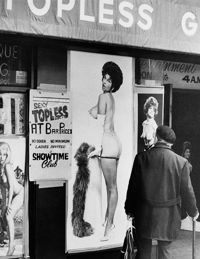 A man walking past the entrance to a topless bar in Times Square, New York City, 1975.