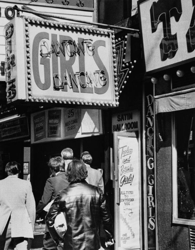 Men walking past the entrance to one of the strip clubs around Times Square, New York City, 1975.