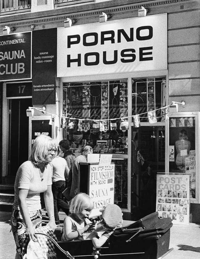 Street scene showing a sex shop and massage parlour titled 'Porno House', New York City, 1975.
