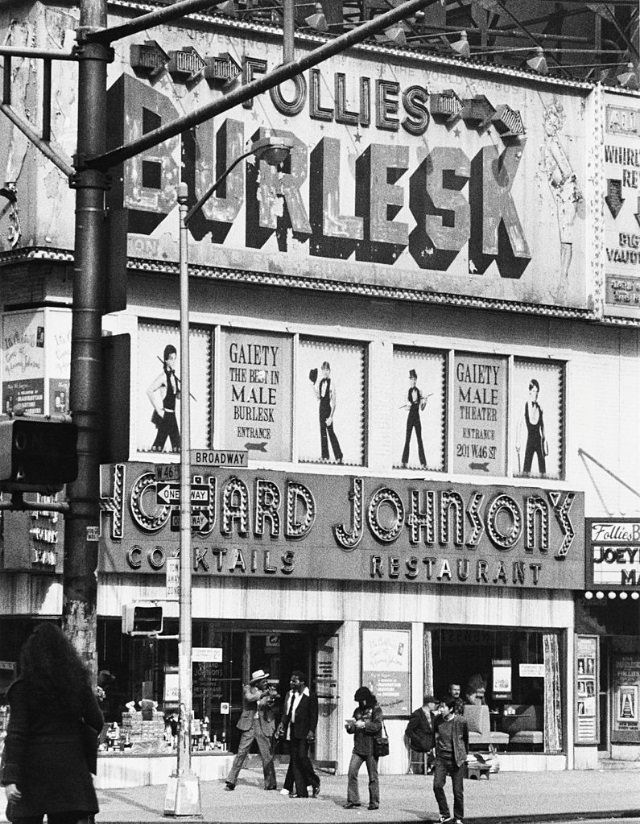 The 'Follies Burlesk' showing the upcoming show for the 'Gaiety Male Theater' above 'Howard Johnson's' restaurant on 46th St. and Broadway, New York City, 1978.