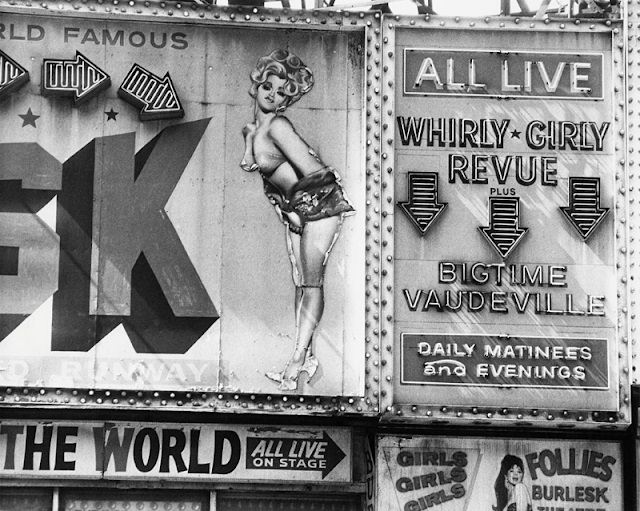 The 'Whirly Girly Revue' and 'Bigtime Vaudeville' strip club signs at the 'Follies Burlesk' on 46th St. and Broadway, New York City, 1978.