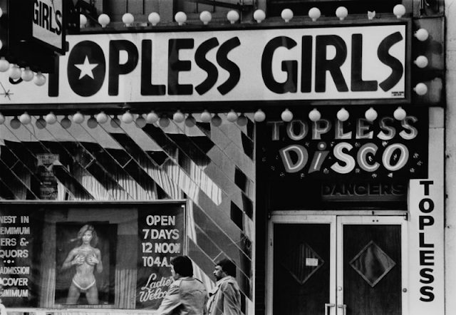 Two men walking past the entrance to a topless disco, New York City, circa 1980.