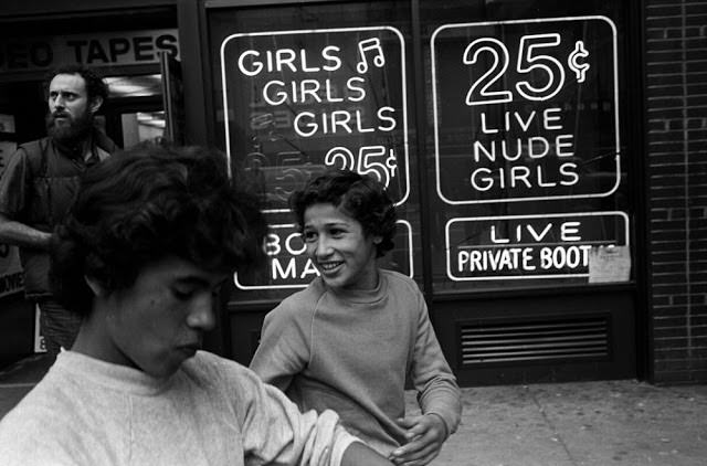 Two teenage hustlers walk by an x-rated video store in Times Square that offered nude girls for 25 cents.
