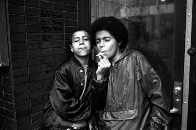 Child prostitutes or also known as teenage hustlers share a cigarette while waiting for customers on 7th Avenue near 42nd Street.