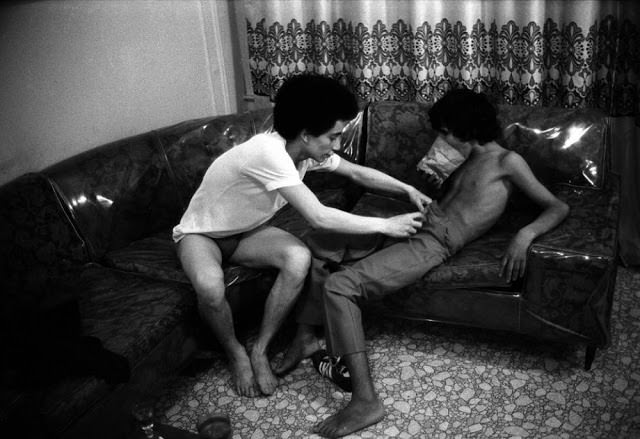 A 16-year-old child prostitute (right) sniffs glue out of a paper bag as his friend (left), an older hustler, undresses him in 1979.