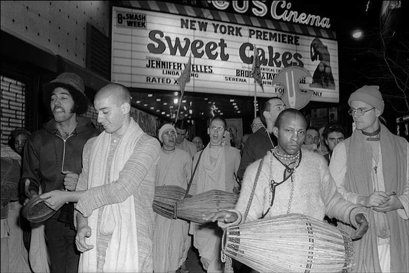 In 1976, a group of Hare Krishna followers sing and play instruments in Times Square under the marquee of an adult theater advertising the film Sweet Cakes.