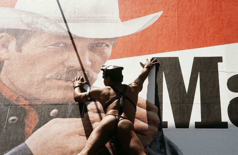 A man adorning only a leather hat and thong scales a Marlboro billboard on 44th Street in 1980.