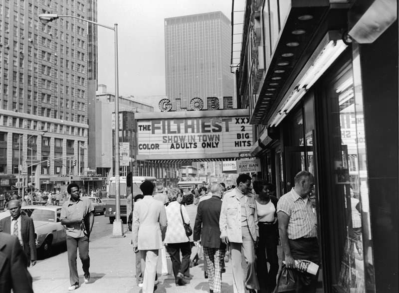 """Tourists looking into the windows of Times Square as they pass under the marquee for the Globe theater advertising the """"filthiest show in town."""", 1975."""