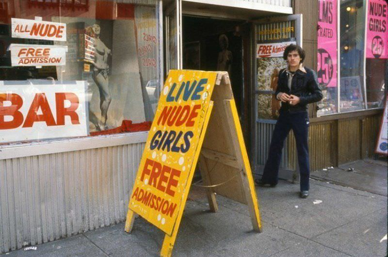 A man stands outside of a strip club on 42nd Street in the late 1970s.