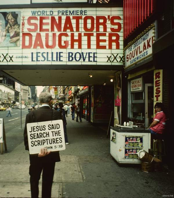 A Christian proselytizer walks in front of an adult theater on 8th Avenue.