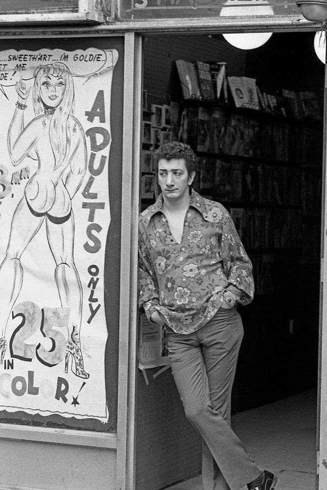 A salesman at a sex shop surveys his storefront as he waits for customers to stroll by. 1970