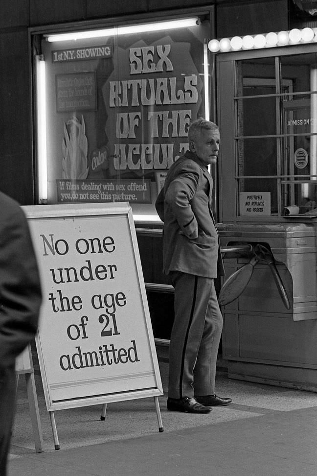 An usher stands near the box office of a movie theater that screens pornography films. No one under the age of 21 would be let in.