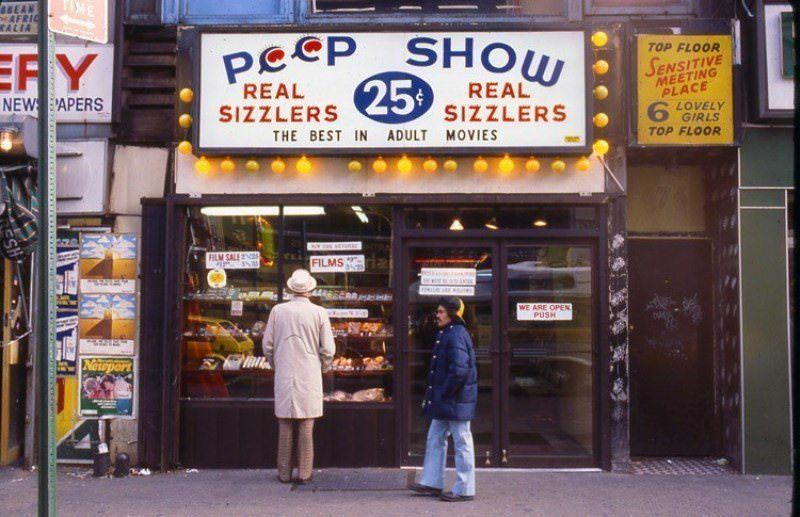 """A man looks at the offerings of a peep show store adjacent to a """"sensitive meeting place"""" with """"lovely girls."""" Brothels, typically operated by organized crime, ran in the open without any legal repercussions."""