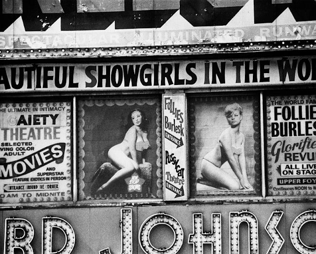 Posters advertising burlesque shows at the Follies Burlesk and Gaiety Theater in in Times Square, New York City, 1975.