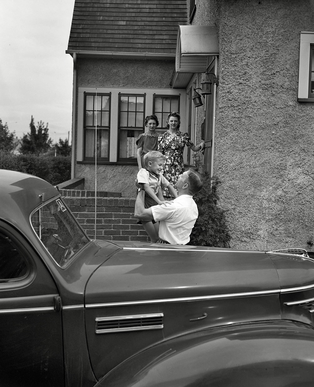 Babcock, Shirley and Earl greeting Mr. Babcock in front of the house, New York, September 1942