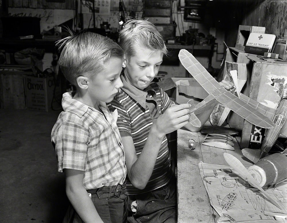 Earl and Howard Babcock looking over one of the model airplanes which Howard built, New York, September 1942