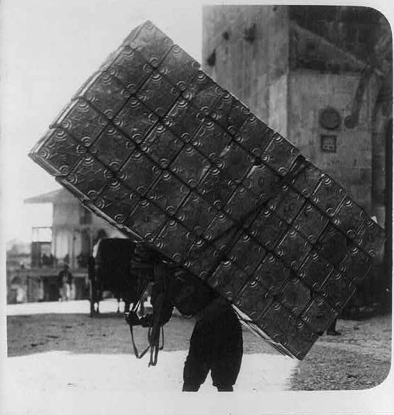A porter carrying 50 empty petrol tins on his back, Circa 1914-1918