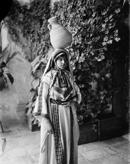 A woman poses with a jug on her head.Ramallah, Circa 1898-1914