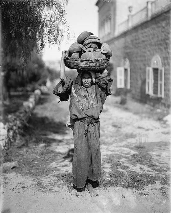 A woman carries her wares to the marketplace, Circa 1898-1914