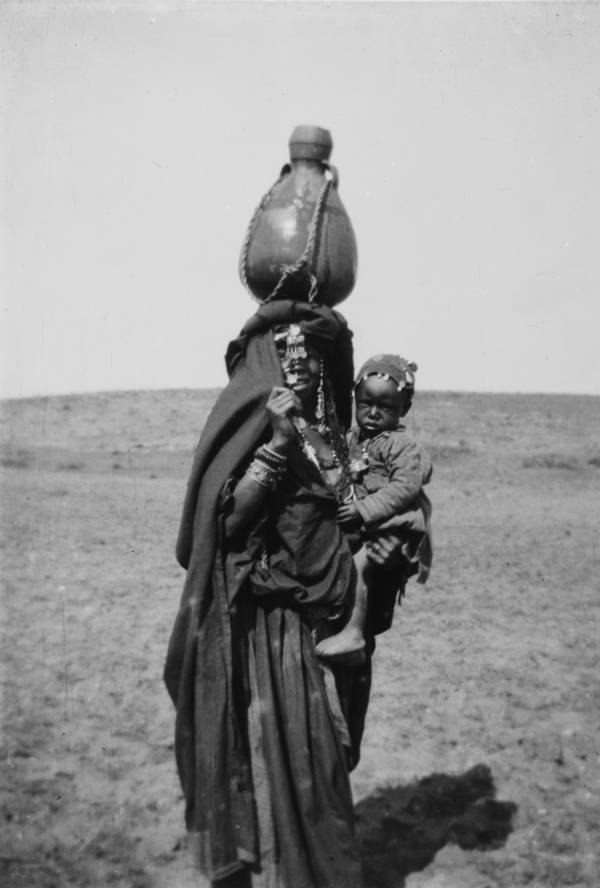 A mother carries her child with a jug on her head.Beersheba, Circa 1900-1920