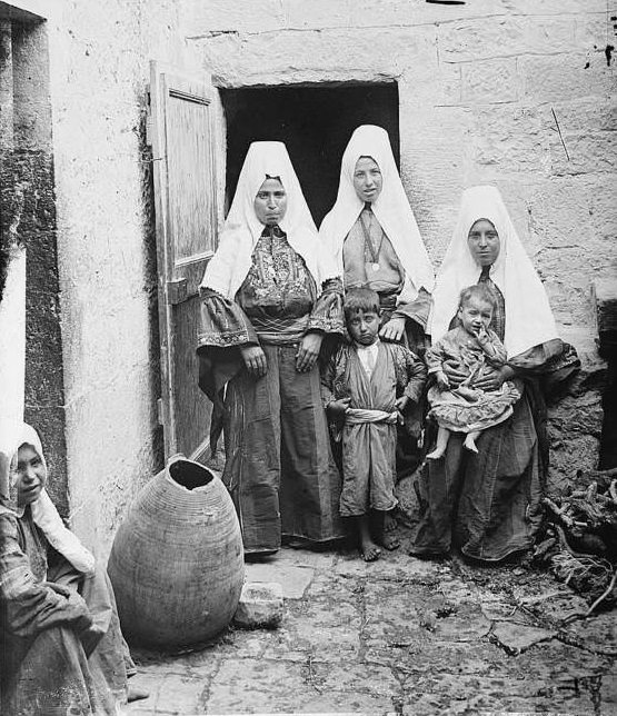 Three women stand by the door with their children.Bethlehem, 1936