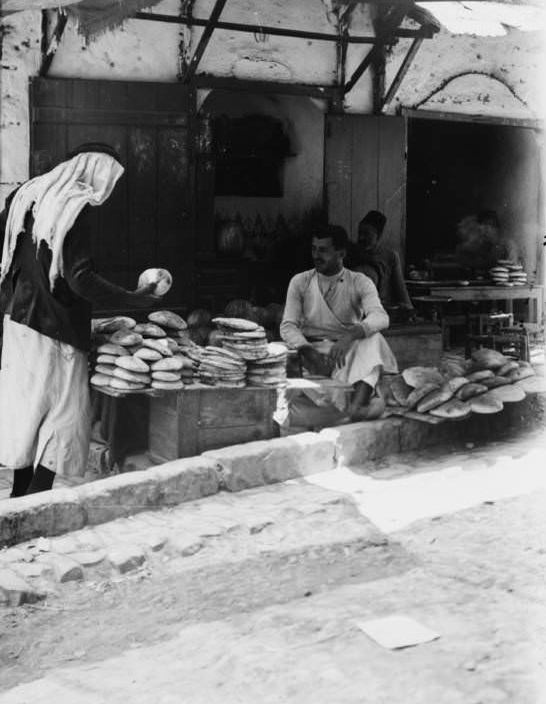 A woman barters over the price of bread, Circa 1900-1920
