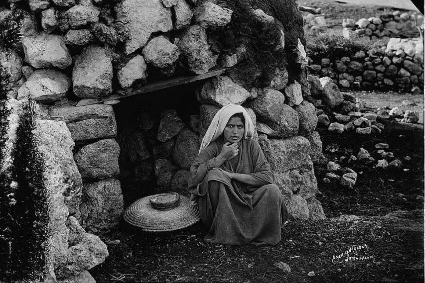 A woman sits in front of the village oven, Circa 1898-1914