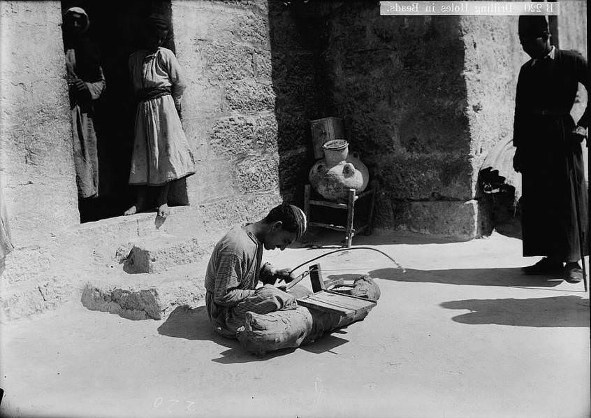 A worker drills holes into beads, Circa 1900-1920