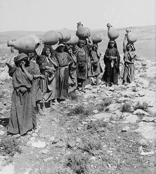 A group of women carrying water jars on their heads, Circa 1900-1920