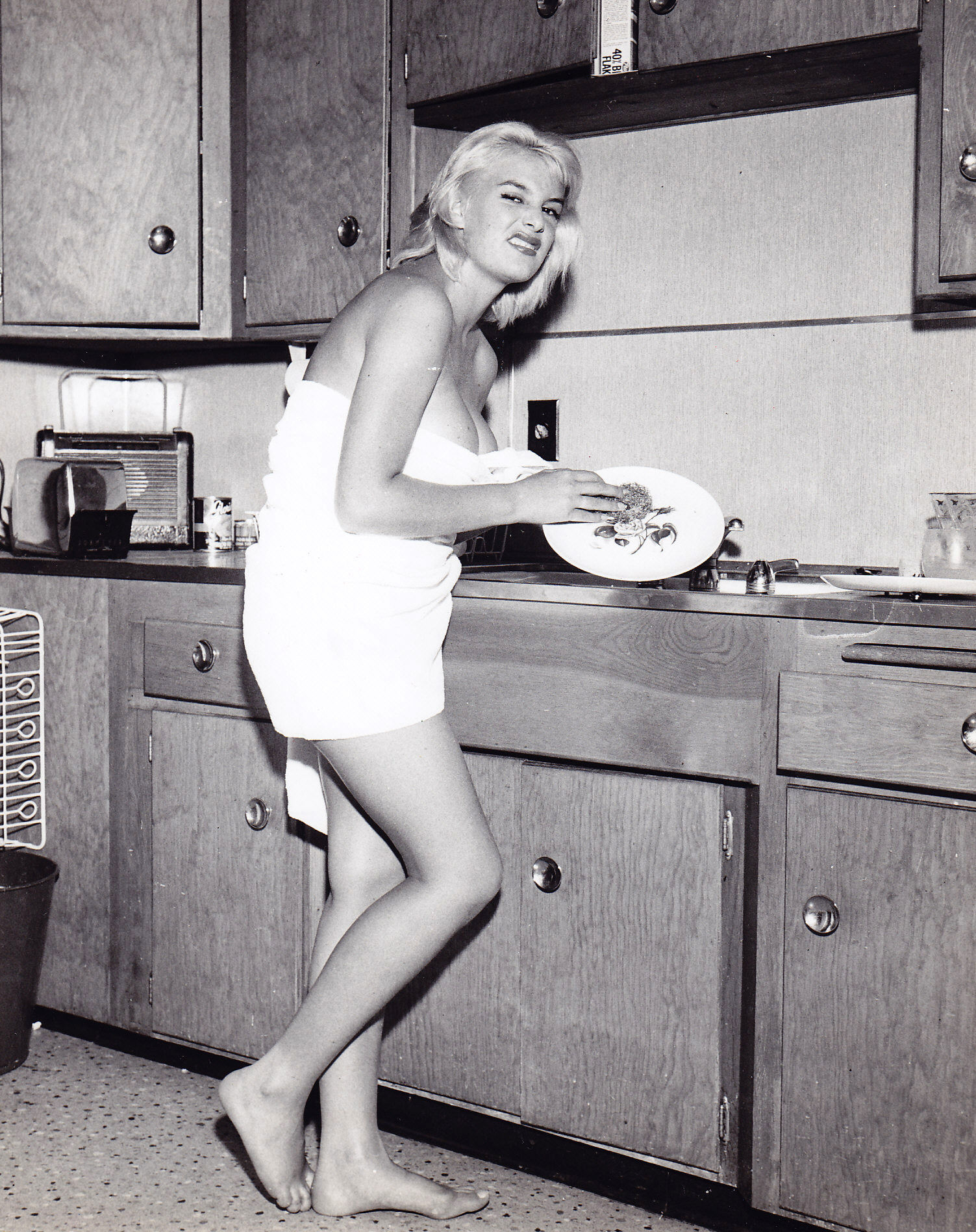 June Wilkinson doing the dishes in the kitchen, 1957