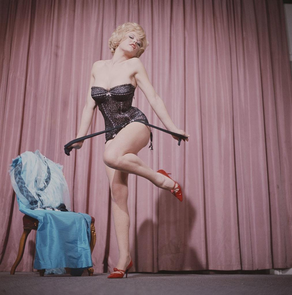 Margaret Nolan in a basque and red heeled shoes whilst performing a striptease routine on stage circa 1965.