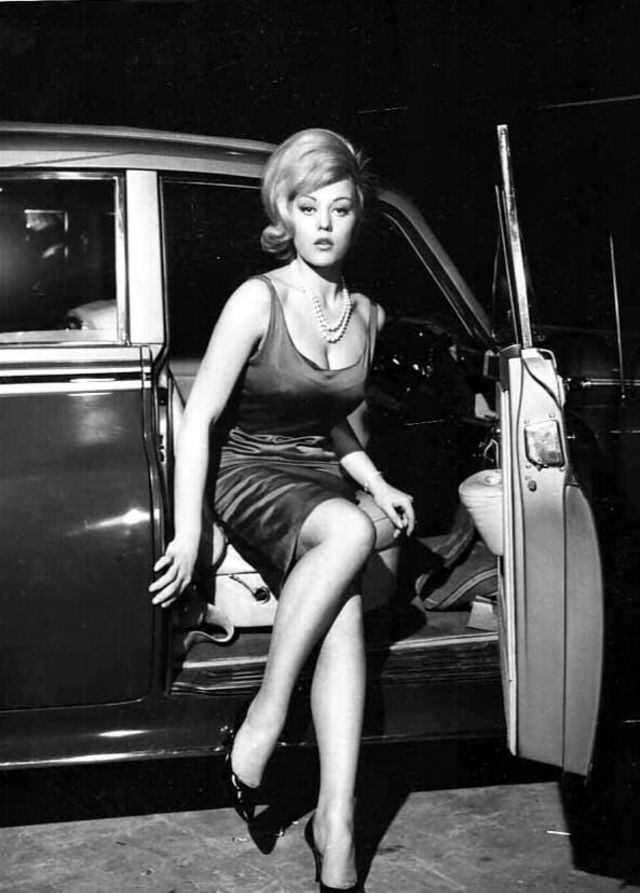 Margaret Nolan getting out of a car to attend a party