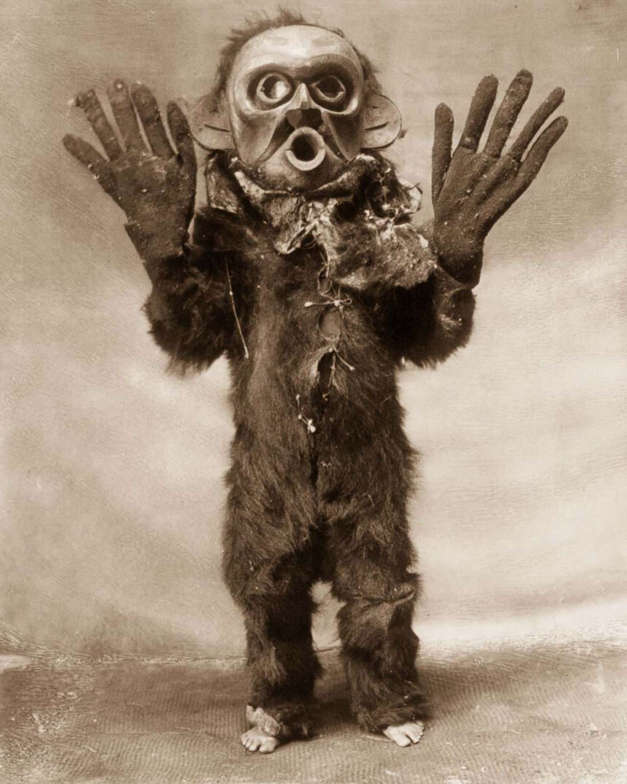 """A Koskimo man dressed as Hami (""""dangerous thing"""") during a Numhlim ceremony. 1914."""