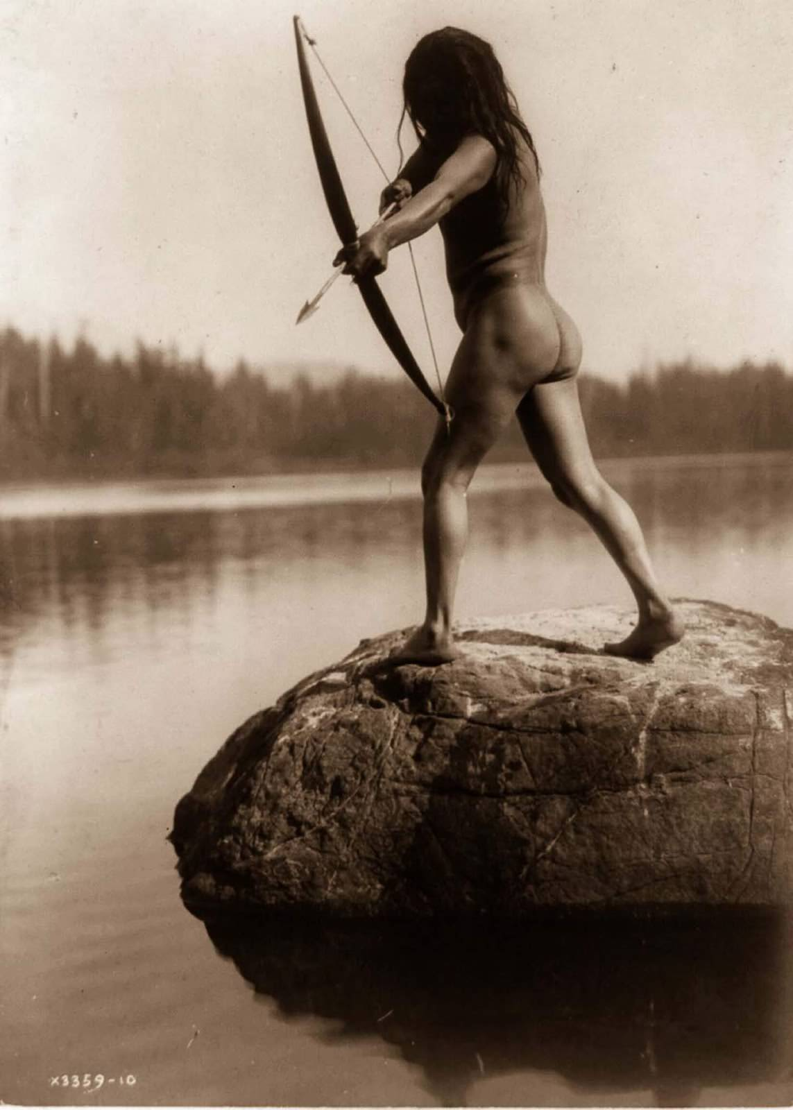 A Nootka man aims a bow and arrow. 1910.