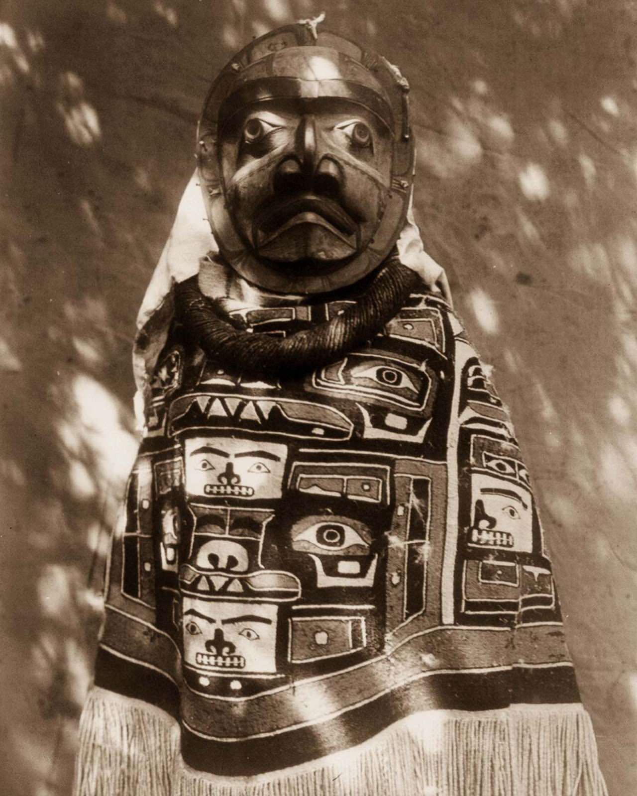A Qagyuhl woman wears a fringed Chilkat blanket and a mask representing a deceased relative who had been a shaman. 1914.