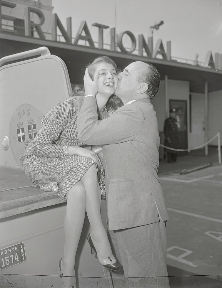 Pier Angeli being welcomed by Leonide Moguy with a kiss at Idlewild Airport, 1952