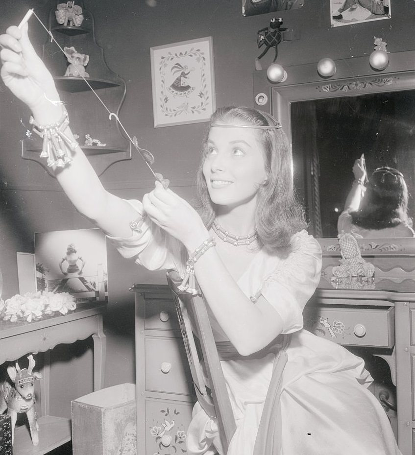 Pier Angeli tries out a model airplane given her by the cast of The Silver Chalice, 1954