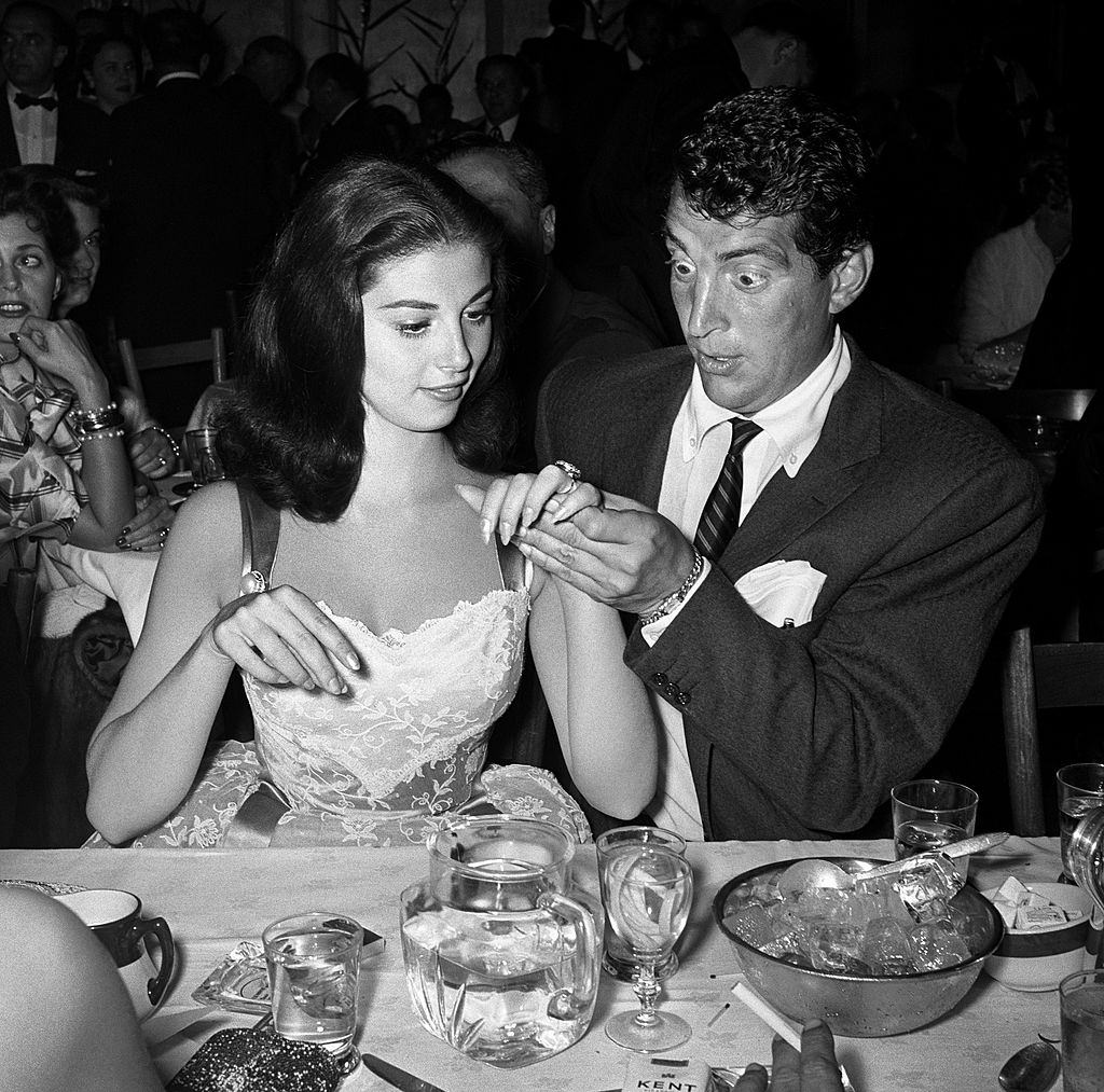 Pier Angeli shows off her engagement ring to a wide-eyed Dean Martin in 1955