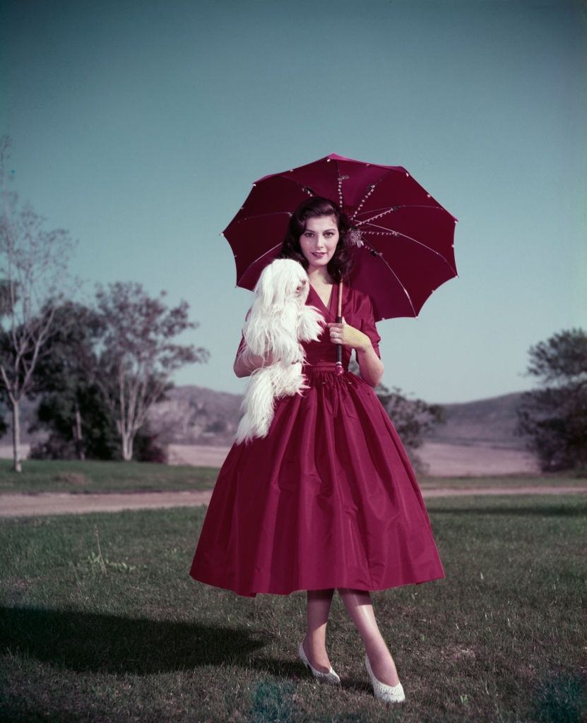 Pier Angeli wearing a red dress and matching parasol, and holding a small white dog, circa 1955