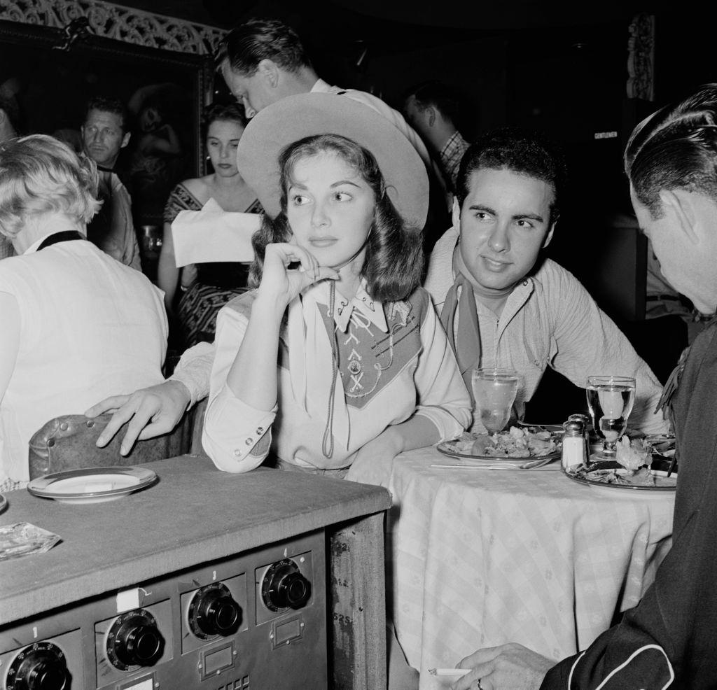Pier Angeli with Alan Pearl dressed in western attire at a party, circa 1955